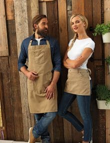 Man and woman wearing matching chino aprons