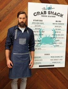 Waiter wearing blue denim contrast apron