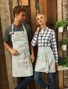 Man wearing cotton bib apron, waitress wearing waist apron